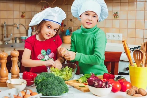 Szczęśliwa Rodzina śmieszne Dzieci Przygotowują Sałatkę Ze świeżych Warzyw W Kuchni Darmowe Zdjęcia