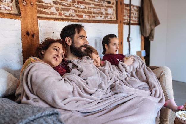Szczęśliwa Rodzina W Domu Ogląda Filmy Na Kanapie I Je Popcorn Premium Zdjęcia