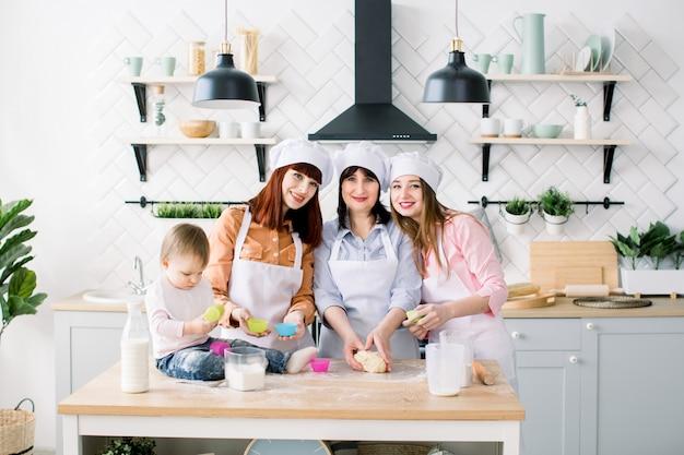 Szczęśliwa Rodzina W Kuchni. Młoda Kobieta I Jej Siostra, Kobieta W średnim Wieku I Mała śliczna Córka Gotuje Babeczki Na Dzień Matki, Seria Zdjęć O Codziennym Stylu życia W Prawdziwym Wnętrzu Premium Zdjęcia