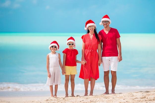 Szczęśliwa rodzina z dwójką dzieci w santa hat na wakacje Premium Zdjęcia