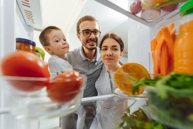 Szczęśliwa Rodzina Z Produktami W Pobliżu Lodówki W Kuchni. Koncepcja Szczęśliwej Rodziny. Zdrowe Odżywianie Premium Zdjęcia