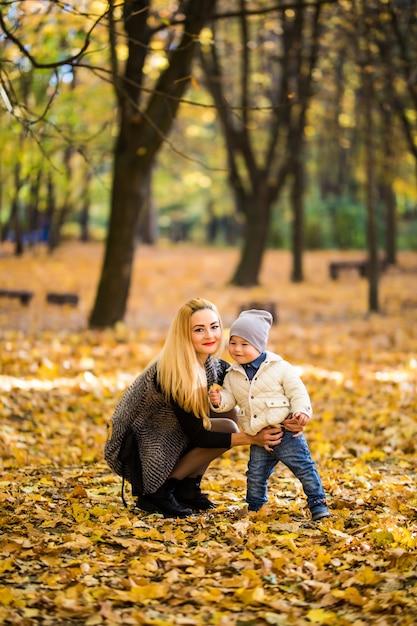 Szczęśliwa Rodzina Zabawy Na świeżym Powietrzu W Jesiennym Parku Przed Niewyraźnymi Liśćmi Darmowe Zdjęcia