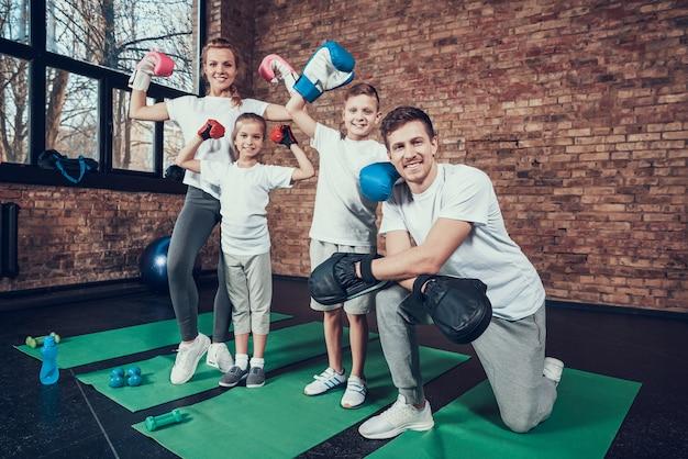 Szczęśliwa rodzina zwycięzców stojących na siłowni. Premium Zdjęcia