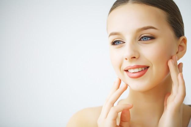 Szczęśliwa roześmiana młoda kobieta o doskonałej skórze, naturalnym makijażu i pięknym uśmiechu. portret kobiecy z odsłoniętymi ramionami Premium Zdjęcia