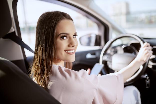 Szczęśliwa śliczna Kaukaska Brunetka Jedzie Jej Samochód I Używa Mądrze Telefon Podczas Gdy Patrzejący Kamerę. Zdjęcie Zrobione Z Tylnego Siedzenia. Premium Zdjęcia