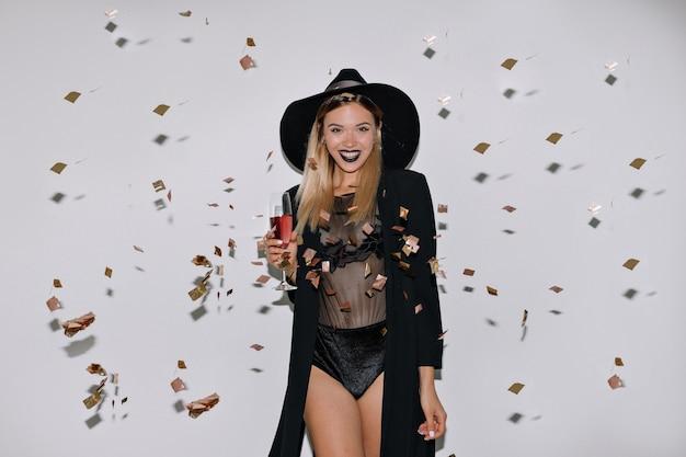 Szczęśliwa śliczna Kobieta O Blond Włosach Z Winem Na Odizolowanej ścianie Z Konfetti Darmowe Zdjęcia