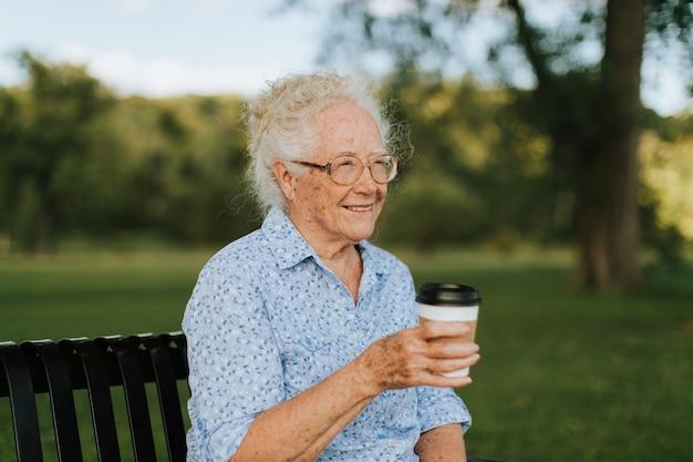 Szczęśliwa starsza kobieta ma takeaway kawę przy parkiem Premium Zdjęcia