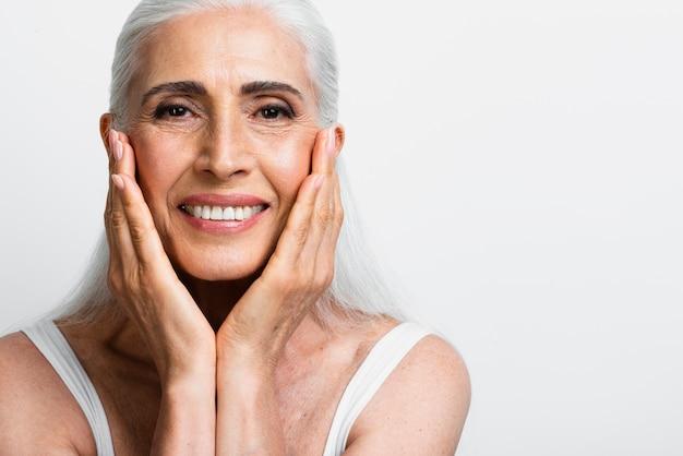 Szczęśliwa starsza kobieta stosuje skincare śmietankę Darmowe Zdjęcia