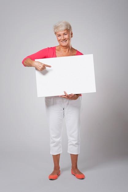 Szczęśliwa Starsza Kobieta, Wskazując Na Tablicy Darmowe Zdjęcia