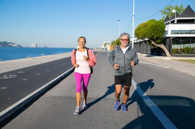 Szczęśliwa Starsza Para Jogging Wzdłuż Brzegu Rzeki. Siwy Mężczyzna I Kobieta W Strojach Sportowych, Biegający Na Zewnątrz. Koncepcja Aktywności I Wieku Darmowe Zdjęcia