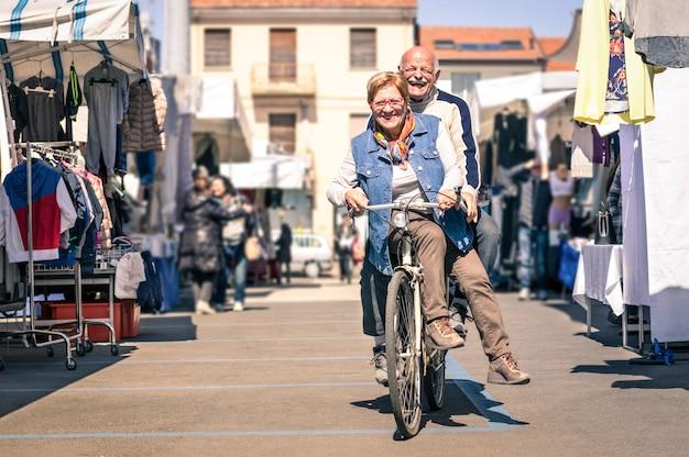 Szczęśliwa Starsza Para Ma Zabawę Z Bicyklem Przy Pchli Targ Premium Zdjęcia