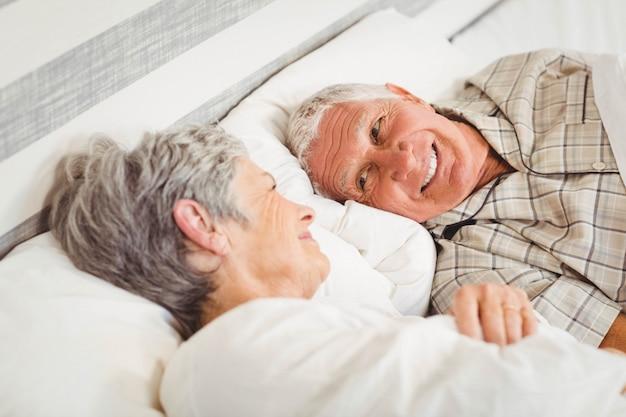 Szczęśliwa starsza para śmia się na łóżku w sypialni Premium Zdjęcia