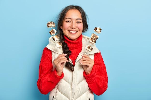 Szczęśliwa Uśmiechnięta Azjatka Trzyma Kije Z Aromatycznymi Pysznymi Pieczonymi Piankami Marshmallows, Lubi Piknik Na Wsi, Nosi Ciepłe Ubrania Darmowe Zdjęcia