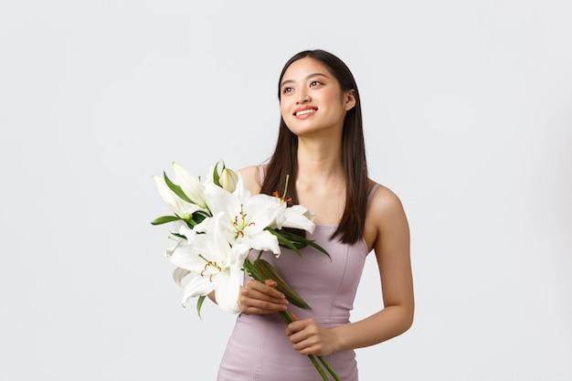 Szczęśliwa Uśmiechnięta Azjatycka Kobieta W Stylowej Sukience, Patrząc W Lewym Górnym Rogu I Trzymając Bukiet Lilii Darmowe Zdjęcia
