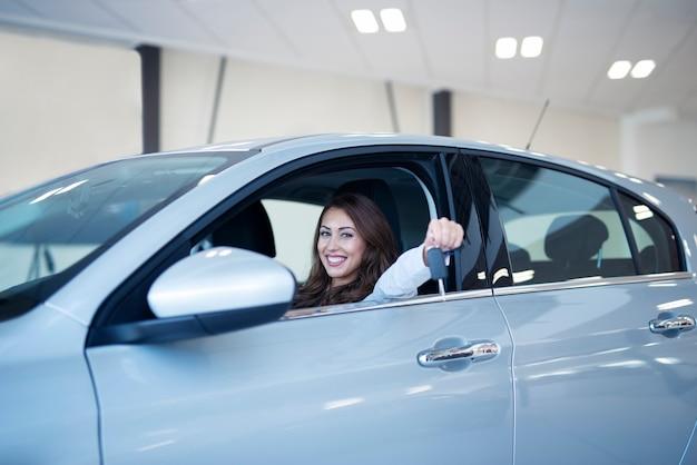 Szczęśliwa Uśmiechnięta Kobieta Trzyma Klucze Swojego Nowego Pojazdu Darmowe Zdjęcia