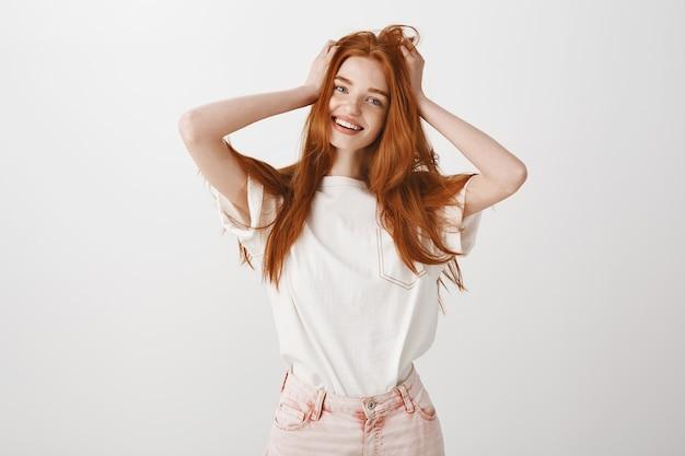Szczęśliwa Uśmiechnięta Ruda Dziewczyna Dotyka Jej Włosów Darmowe Zdjęcia