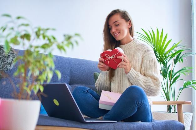 Szczęśliwa Uśmiechnięta Zadowolona Ukochana Kobieta Otrzymała Prezent Online I Trzyma Pudełko W Kształcie Serca Na Walentynki 14 Lutego Premium Zdjęcia