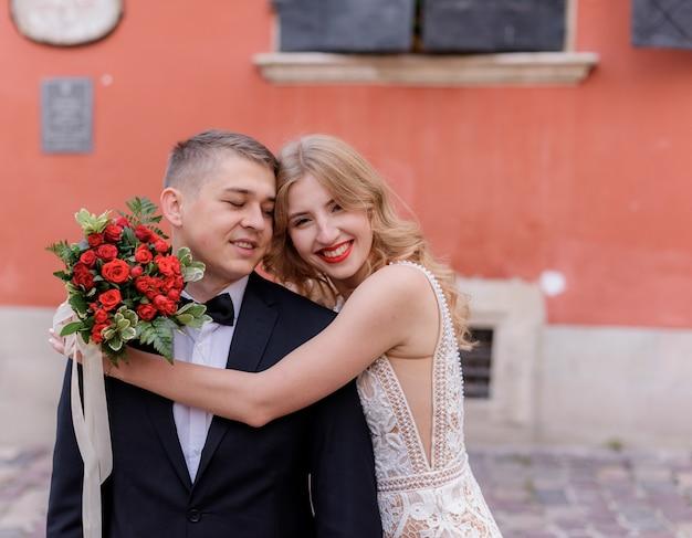 Szczęśliwa Uśmiechnięty ślub Para ściska Przed Czerwoną ścianą Na Zewnątrz, Dzień ślubu, Oficjalne Małżeństwo Darmowe Zdjęcia
