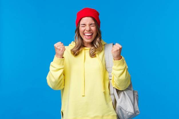 Szczęśliwa Wesoła Blond Dziewczyna W Czerwonej Czapce I żółtej Bluzie Z Kapturem, Zamknięte Oczy Z Ulgą I Uśmiechnięta Triumfująca, świętująca Wspaniałe Wieści, Zdała Egzaminy Na Uniwersytecie, Mistrz Pięści Jak Mistrz, Wygrywająca Nagrodę Premium Zdjęcia