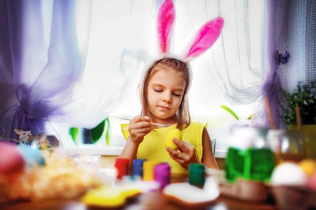 Szczęśliwa Wielkanocna Dziewczyna W Królików Ucho Maluje Jajka, Małe Dziecko W Domu. Ferie Wiosenne Premium Zdjęcia