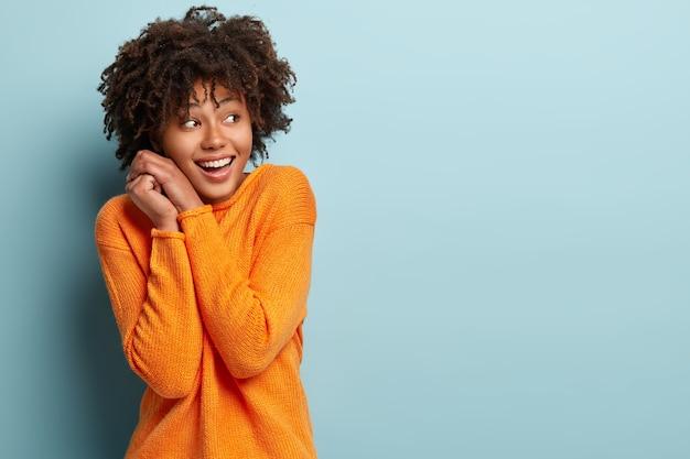 Szczęśliwa, Zadowolona Afroamerykanka Trzyma Ręce Razem Blisko Twarzy, Skupiona, Zauważa Rzeczy Pożądane, śmieje Się, Ubrana W Jasny Sweter, Pozuje Przy Niebieskiej ścianie Z Wolną Przestrzenią Darmowe Zdjęcia