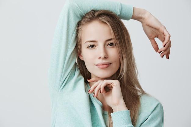 Szczęśliwa Zadowolona Blondynka O Europejskim Wyglądzie Z Ciemnymi Oczami, Ubrana W Niebieski Top Z Długimi Rękawami, Wyglądająca I Uśmiechnięta Darmowe Zdjęcia