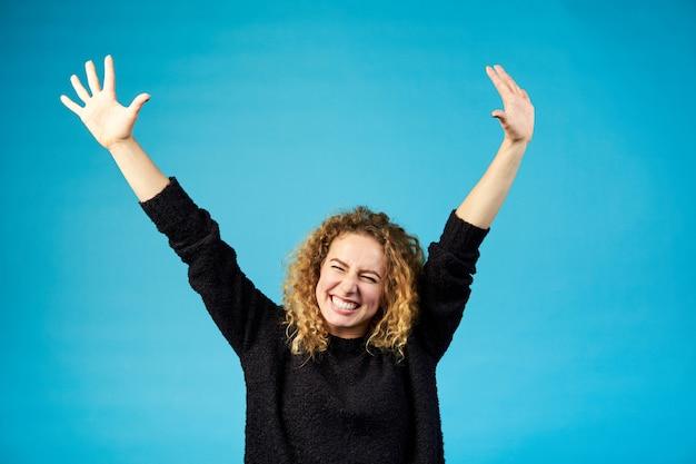 Szczęśliwa zadowolona młoda rudzielec kędzierzawa kobieta świętuje sukces i rozwesela sukces z radością rozprzestrzenia ręki przeciw błękitowi Premium Zdjęcia