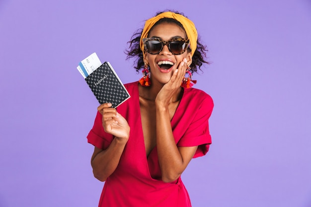Szczęśliwa Zaintrygowana Afrykańska Kobieta W Sukni Trzyma Paszport Z Biletami Premium Zdjęcia