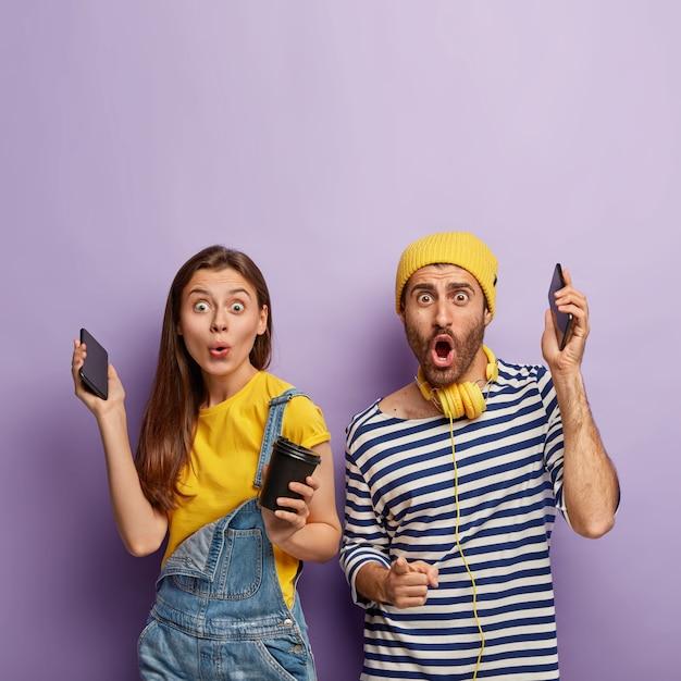 Szczęśliwa Zaskoczona Miła Para Dobrze Się Bawi, Podnosi Ręce Ze Smartfonami, Słucha Przyjemnej Muzyki, Pije Kawę, Cieszy Się Wolnym Czasem, Darmowe Zdjęcia