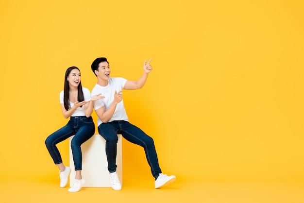 Szczęśliwa Zdziwiona Atrakcyjna Młoda Azjatycka Para Wskazuje Obok I Patrzeje Pustą Przestrzeń W żółtej Odosobnionej Stuidio ścianie Premium Zdjęcia