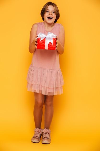Szczęśliwa Zdziwiona Dziewczyny Mienia Czerwieni Teraźniejszość Odizolowywająca Nad Kolorem żółtym Darmowe Zdjęcia
