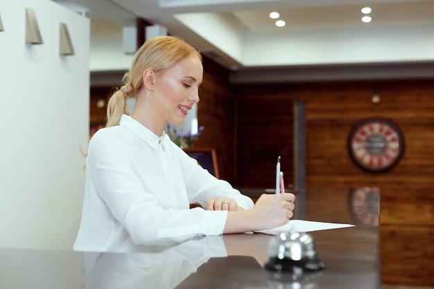Szczęśliwa żeńska Recepcjonistka Stoi Przy Hotelowym Kontuarze Premium Zdjęcia