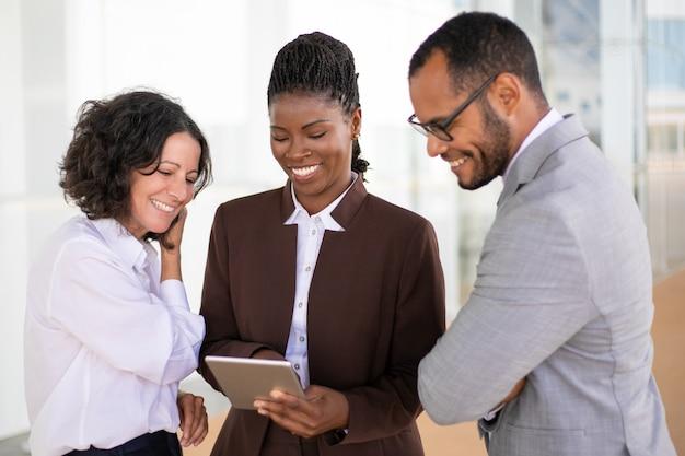 Szczęśliwa zjednoczona biznes drużyna ogląda wideo na pastylce Darmowe Zdjęcia