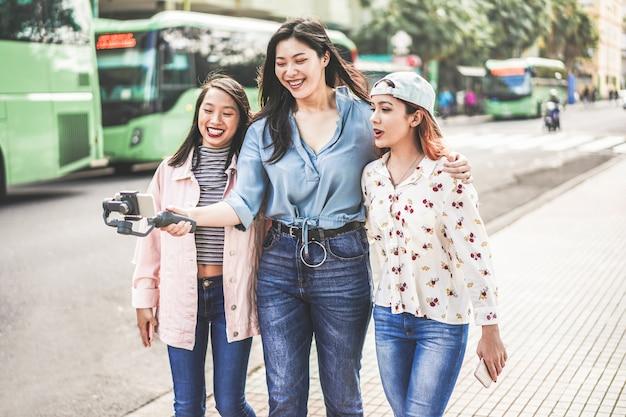 Szczęśliwe Azjatykcie Dziewczyny Robi Vlog Wideo Przy Przystankiem Autobusowym. Modni Przyjaciele Blogujący Dla Mediów Społecznościowych Na Zewnątrz Premium Zdjęcia