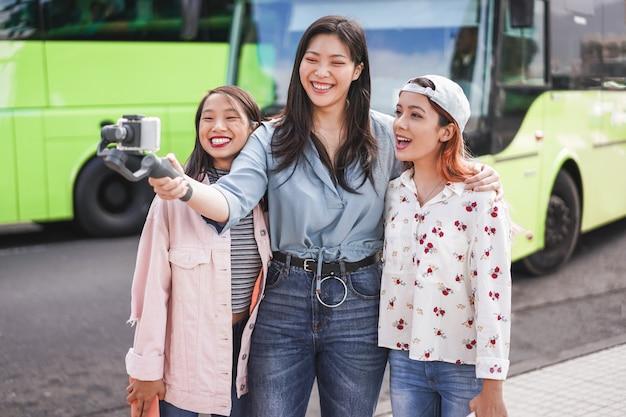 Szczęśliwe Azjatykcie Kobiety Robi Wideo Przy Miasto Przystankiem Autobusowym Premium Zdjęcia