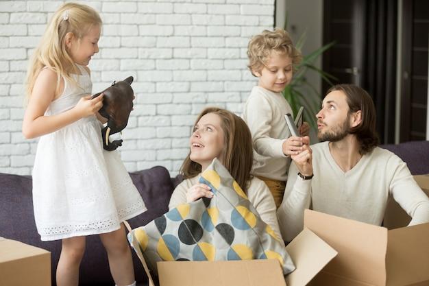 Szczęśliwe dzieci pomagają rodzicom rozpakować pudełka w dniu przeprowadzki Darmowe Zdjęcia