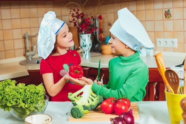 Szczęśliwe Dzieci Przygotowują Sałatki Ze świeżych Warzyw W Kuchni Darmowe Zdjęcia
