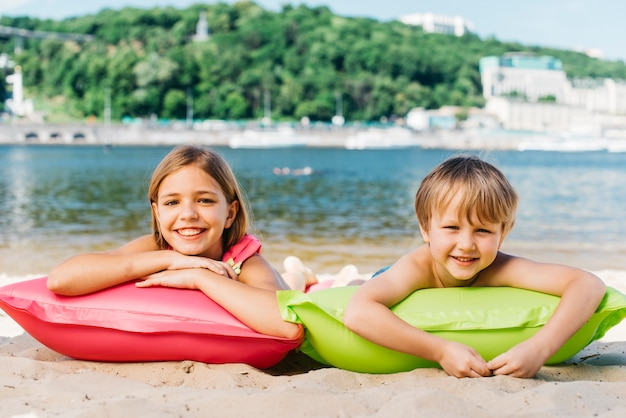 Szczęśliwe dzieci relaks na materacach lotniczych na wybrzeżu rzeki w okresie letnim Darmowe Zdjęcia