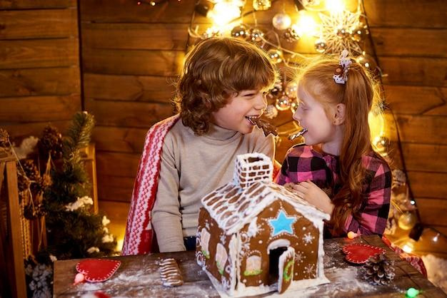 Szczęśliwe Dzieci Z świątecznym Piernikiem W Urządzonym Pokoju Na Wakacje. Premium Zdjęcia
