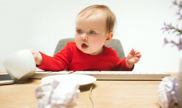 Szczęśliwe Dziecko Dziewczynka Siedzi Z Filiżanką I Klawiaturą Nowoczesnego Komputera Lub Laptopa Na Białym Tle Darmowe Zdjęcia