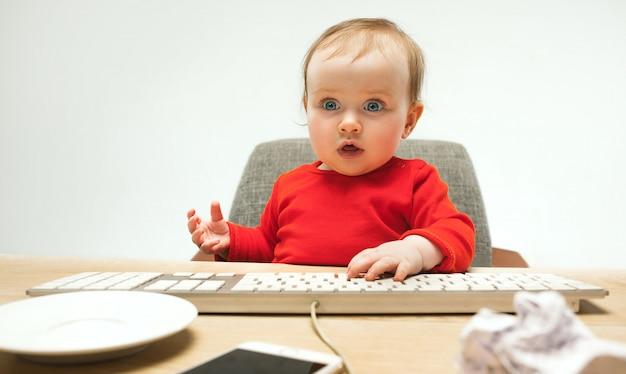 Szczęśliwe Dziecko Dziewczynka Siedzi Z Klawiaturą Nowoczesnego Komputera Lub Laptopa Na Białym Tle Na Białym Studio Darmowe Zdjęcia