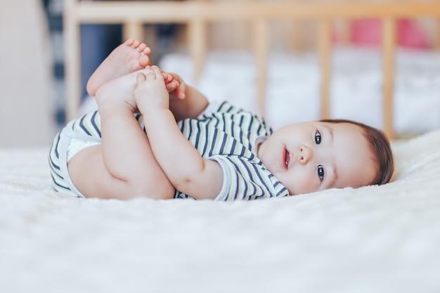 Szczęśliwe Dziecko Leżące Na Białym Prześcieradle I Trzymając Nogi. Zabawne Dziecko Leżące W łóżku Premium Zdjęcia