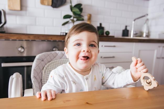 Szczęśliwe Dziecko Siedzi W Krzesełku I śmieje Się W Nowoczesnej Białej Kuchni. Zdrowe Odżywianie Dla Dzieci. Widok Z Boku ładny Maluch Premium Zdjęcia