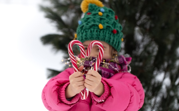 Szczęśliwe Dziecko Z Dużymi Cukierkami Pod Choinką. Koncepcja Ferii Zimowych. Darmowe Zdjęcia