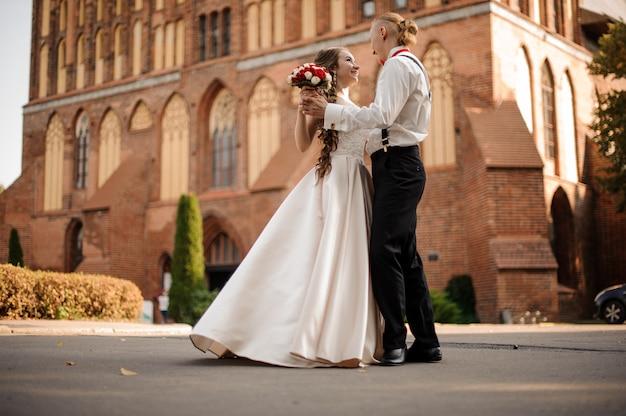 Szczęśliwe I Piękne Małżeństwo Tańczy W Tle Budynku Z Czerwonej Cegły W Słoneczny Dzień Premium Zdjęcia