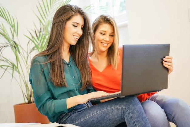 Szczęśliwe Kobiety Używa Komputerowego Notatnika W żywym Pokoju W Domu Premium Zdjęcia