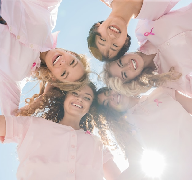 Szczęśliwe kobiety w okręgu z różowymi wstążkami. Premium Zdjęcia