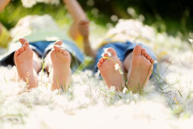 Szczęśliwe małe dzieci, leżące na trawie z piórami, barefo Premium Zdjęcia