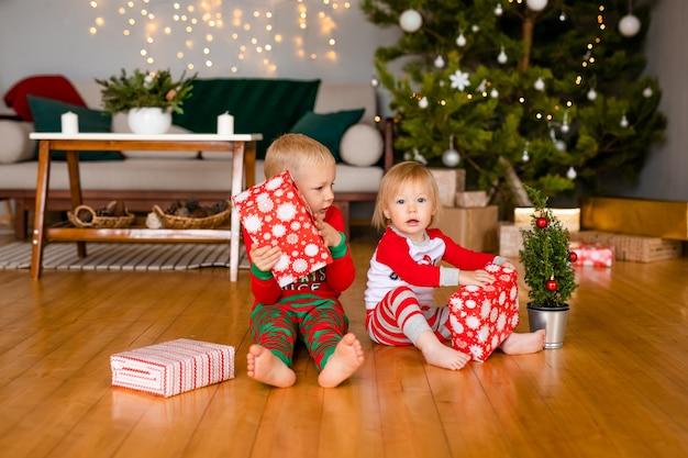 Szczęśliwe Małe Dzieci W Piżamie Bawiące Się Prezentami świątecznymi Premium Zdjęcia