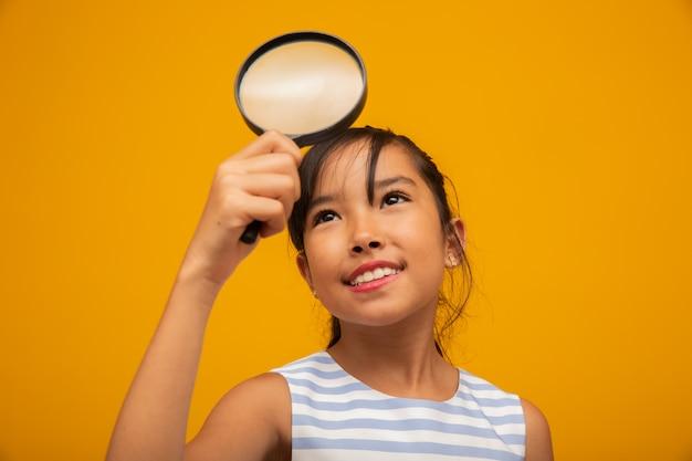 Szczęśliwe małe dziecko azjatyckie z lupą Premium Zdjęcia